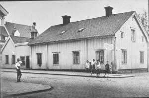 """Ö Storgatan 8 Lekande barn, i korsningen S:t Annegatan / Ö Storgatan, utanför huset som förr benämndes """"Vatten-Anders hus"""", eller som det står på skylten C O Anderssons vattenfabrik, med start 1890, var ett av Nyköpings bryggerier om än bara med läskedrycker."""