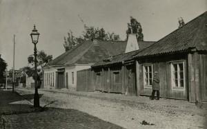 """V Kvarngatan Ännu återstår många gamla byggnader i staden, som dessa i bildens vänstra del, uppförda i tegel omkring 1830. Äldre nyköpingsbor minns dem som """"Källanders"""" efter den bilfirma som huserade där under många år. Detta foto är från omkring 1870, med kullersten och hästlort som goda tidsmarkörer.."""